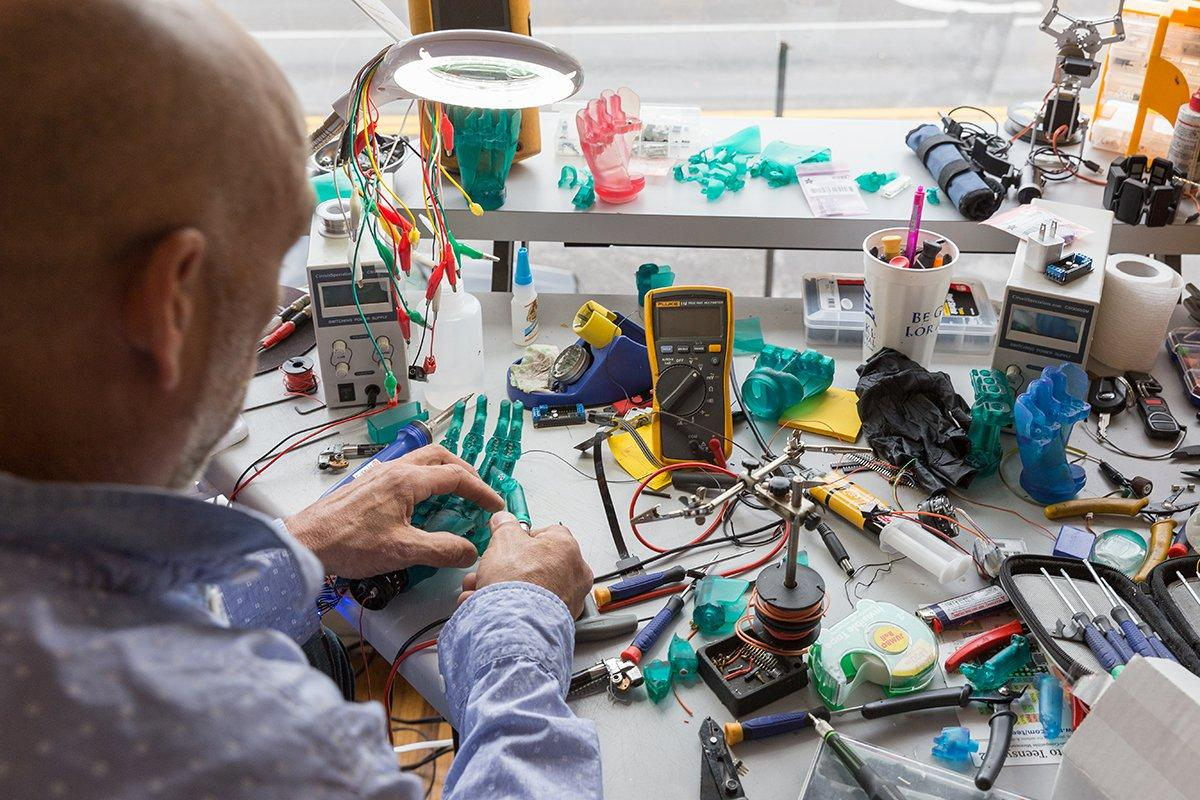 An engineer assembling 3D printed robotic prosthetic hands.